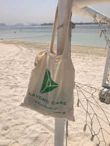A lavorocare Jute Tote bag relaxing on the beach as part of our employee competition : We care about our clients : We care about our Staff : We care about our support workers.